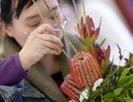 Student creating a flower arrangement
